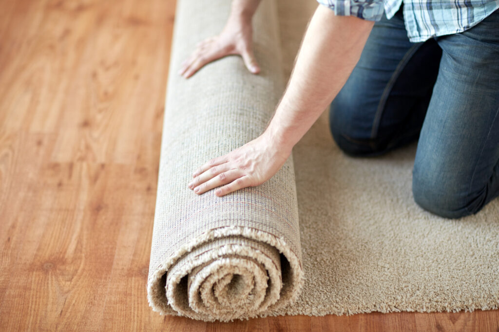 close up of male hands rolling carpet